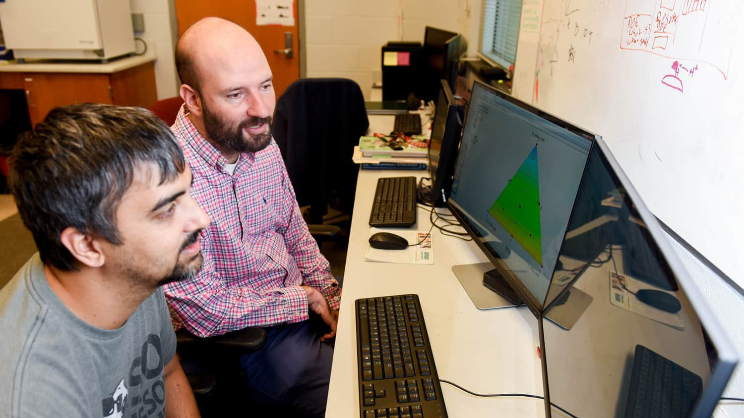 Michael Bereman (right) and graduate student Josh Beri look at a computer in his lab in 2017.