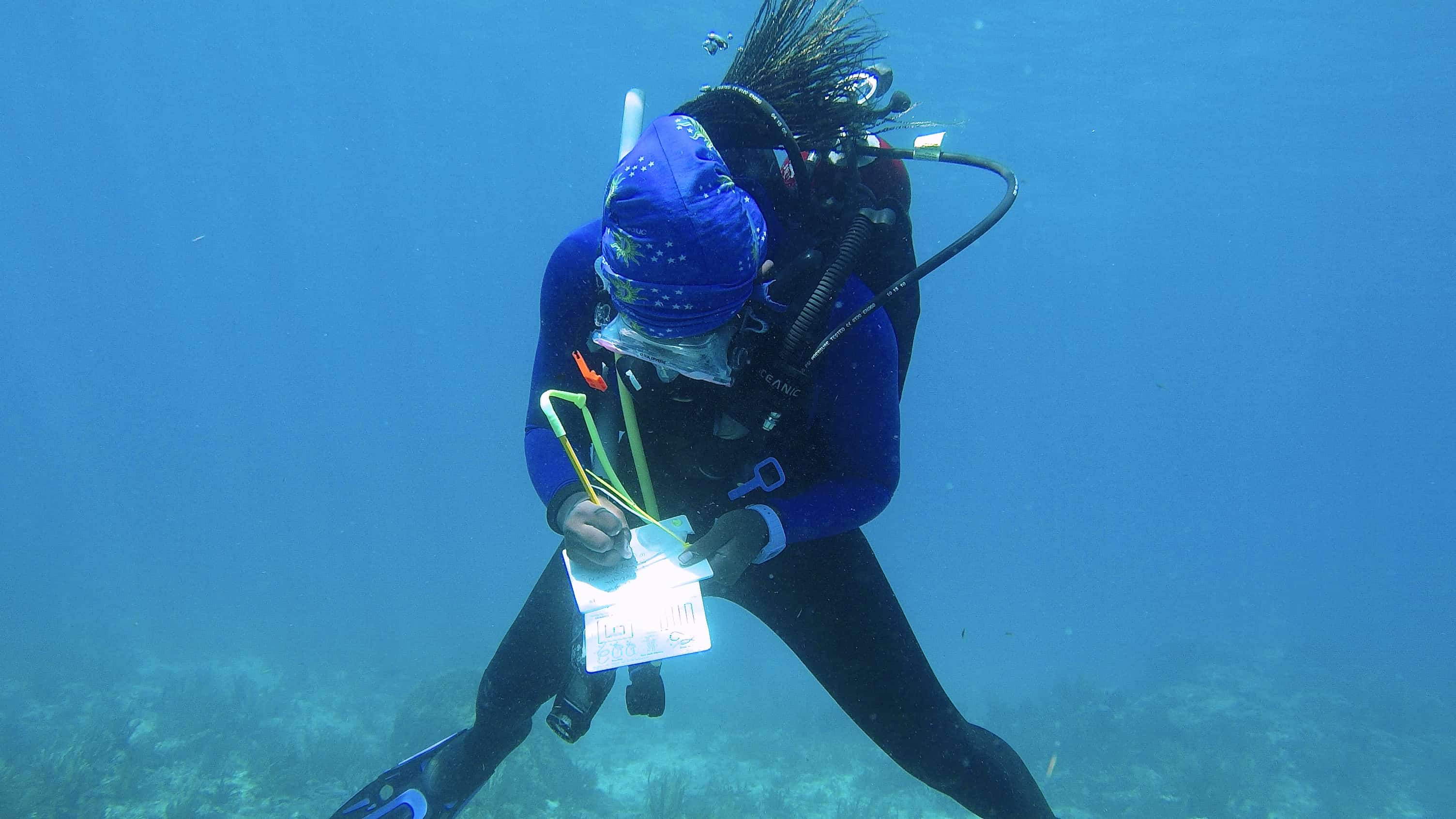 Marine science doctoral student Kayelyn Simmons makes notes while on a research dive studying underwater soundscapes off the Florida Keys.