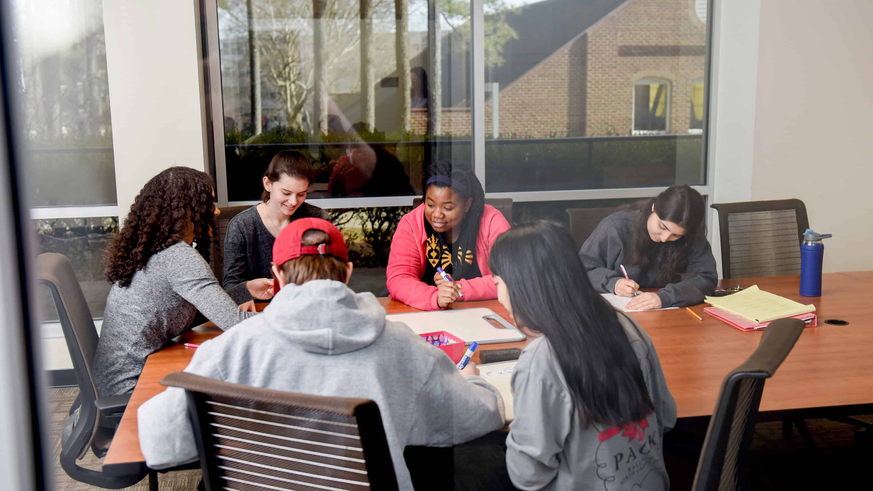 Students working in conference room in WISE Village offices in Lee Hall