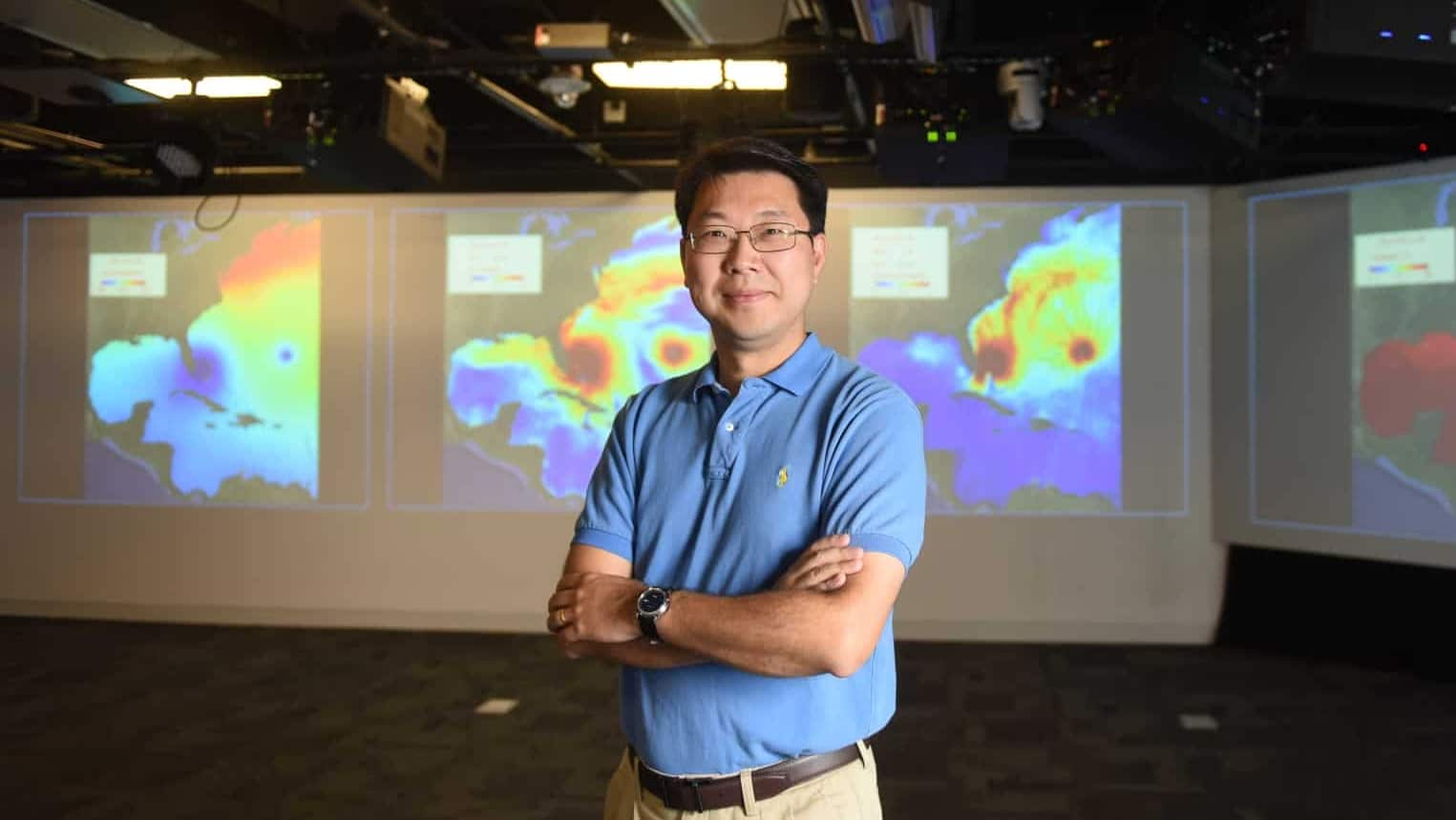Ruoying He in front of a screen displaying ocean weather visualizations