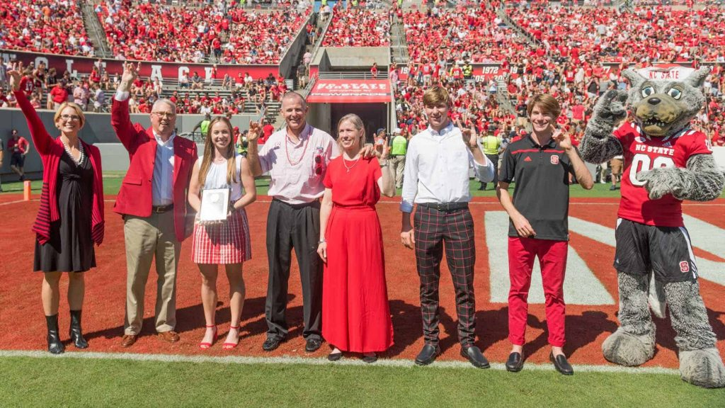 The Verchick family stands on the Carter-Finley football field after receiving the award.