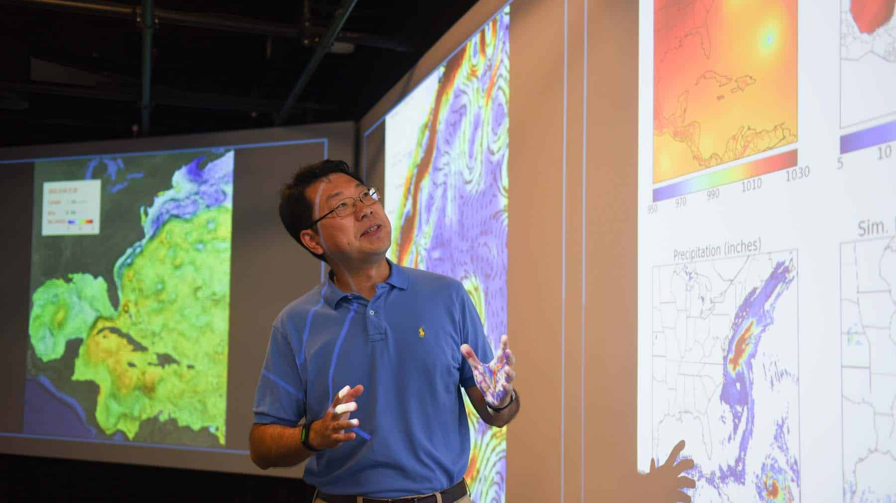 Ruoying He looks at ocean weather visualizations on large screens