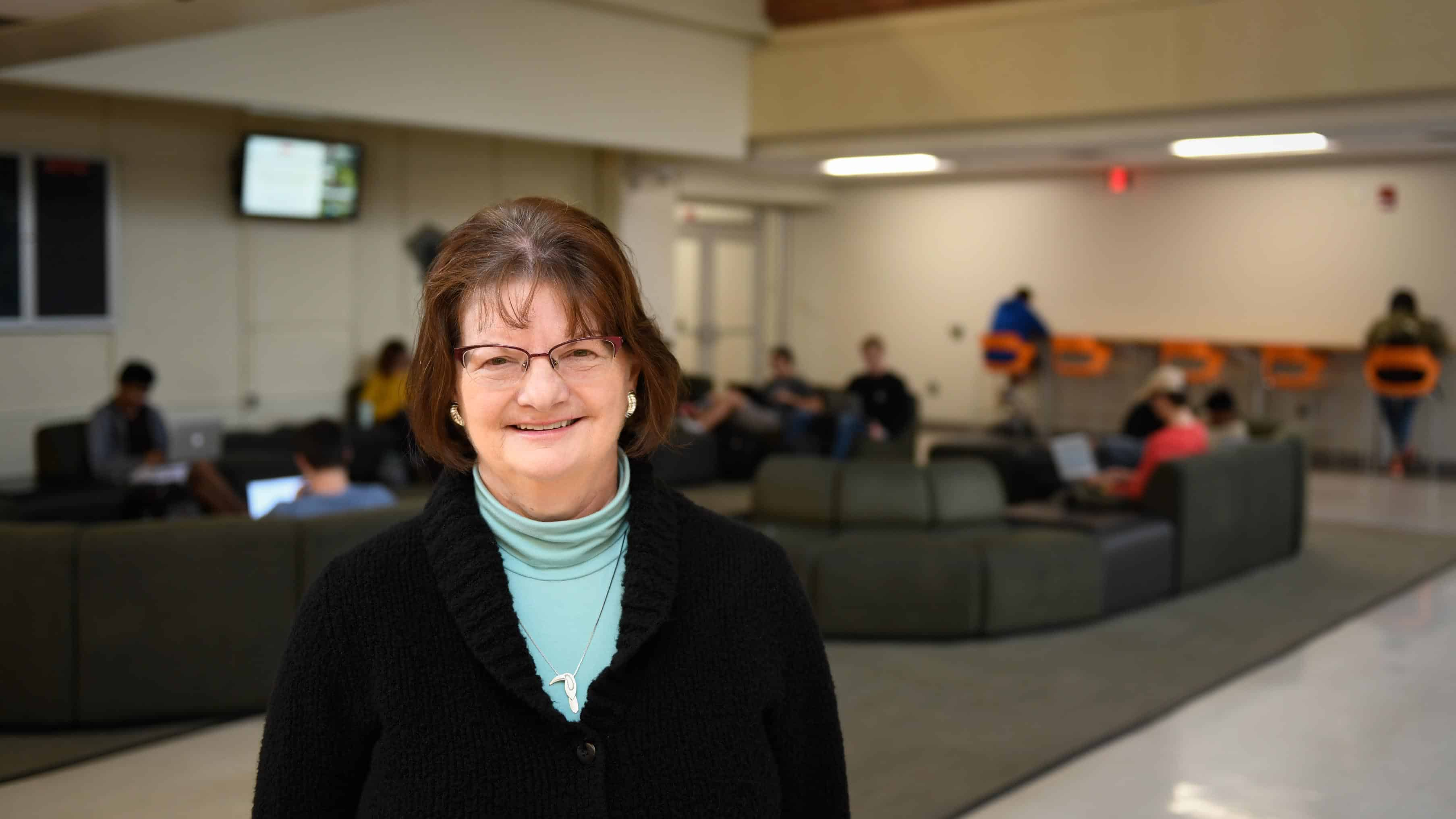 Statistics alumna Nancy Ridenhour in the commons area in Cox Hall with students working in the background