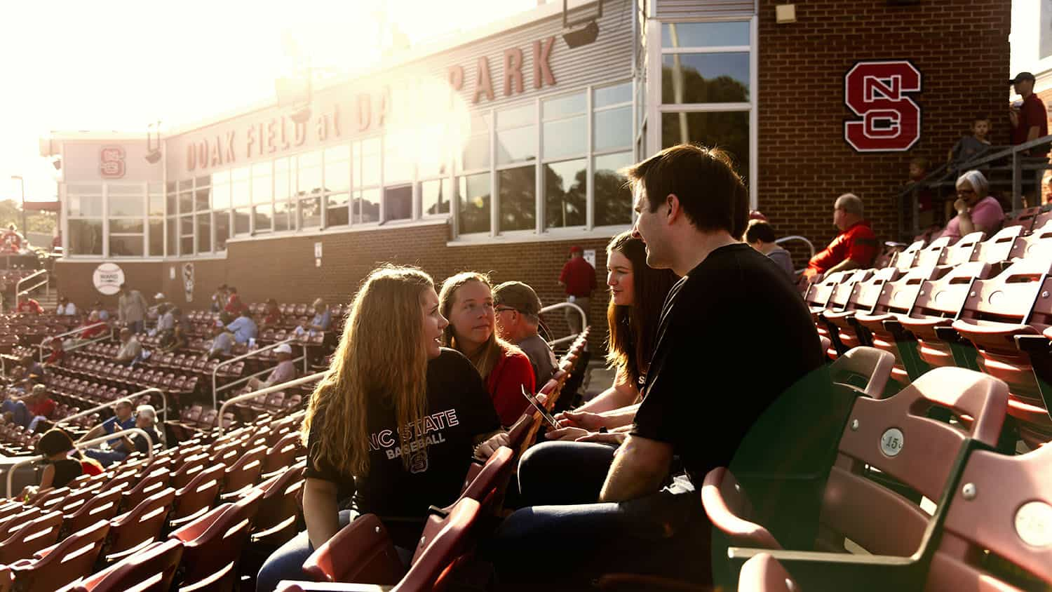 Students collaborating around laptop in baseball stadium stands