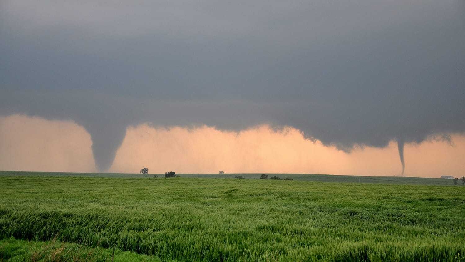 Tornadoes pictured in the distance of a field. Photo from Postdoctoral Research Scholar Brice Coffer.
