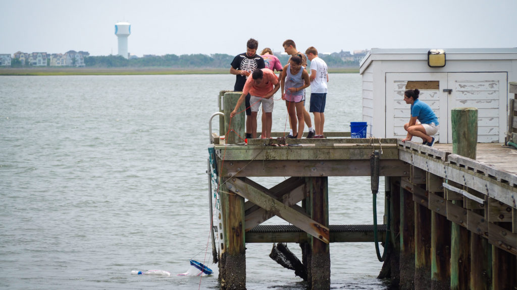 Students dredging for plankton off the pier behind the CMAST building