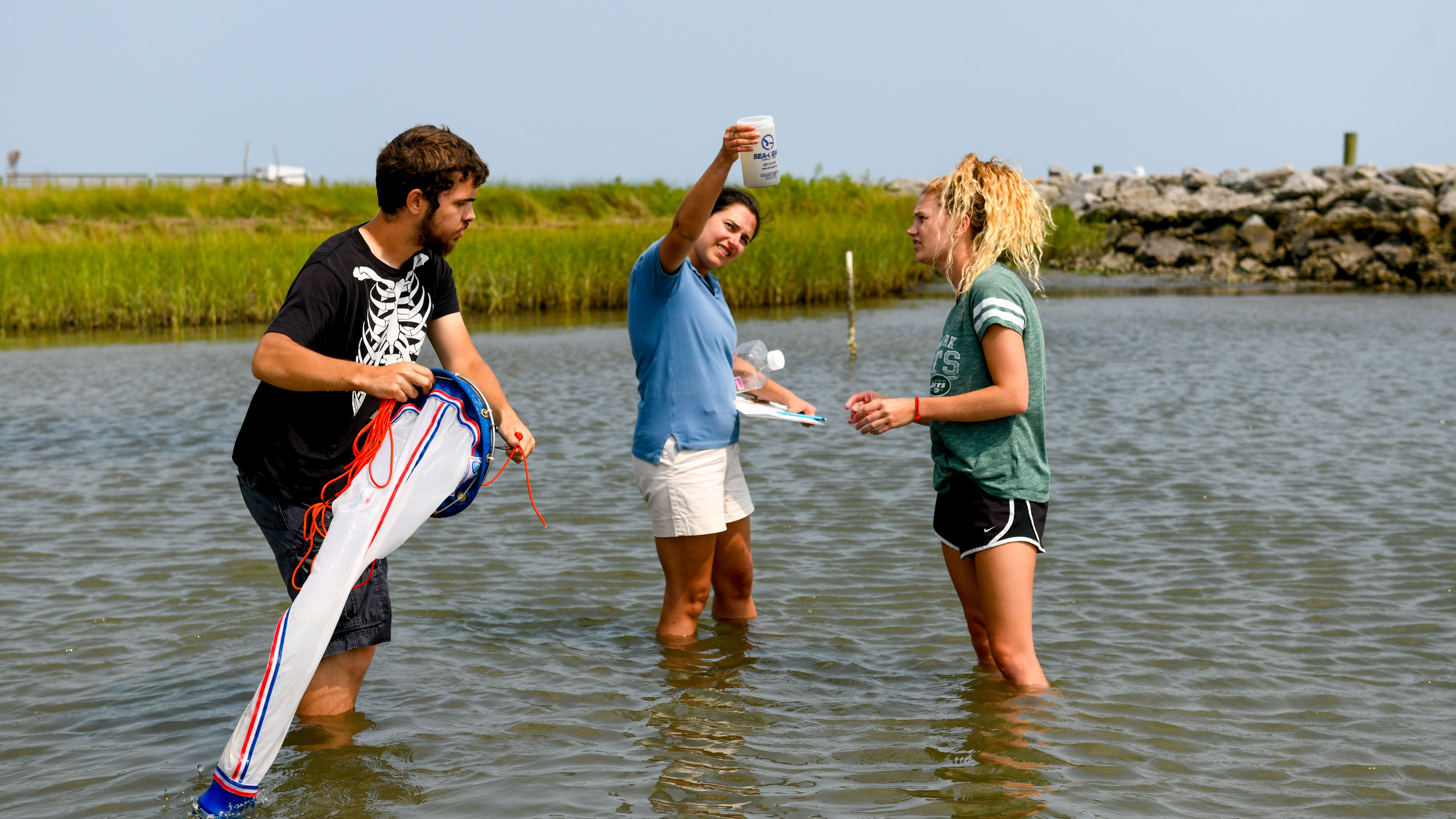 Three people gather samples in knee-deep sound water behind the CMAST building