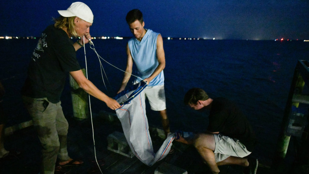 Three males hold a dredging net on a pier at night