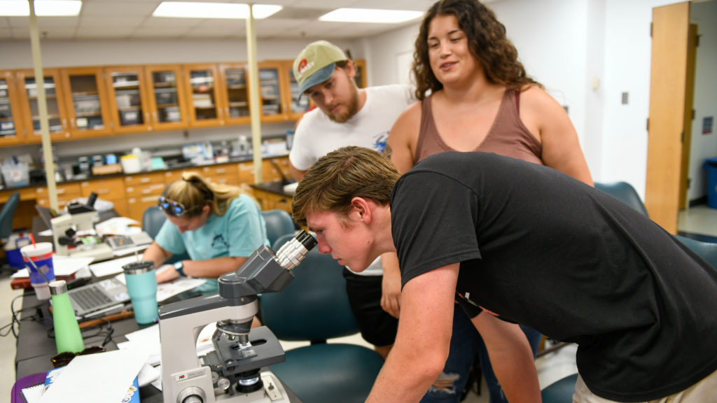 Three students gather around a microscope in a classroom at CMAST