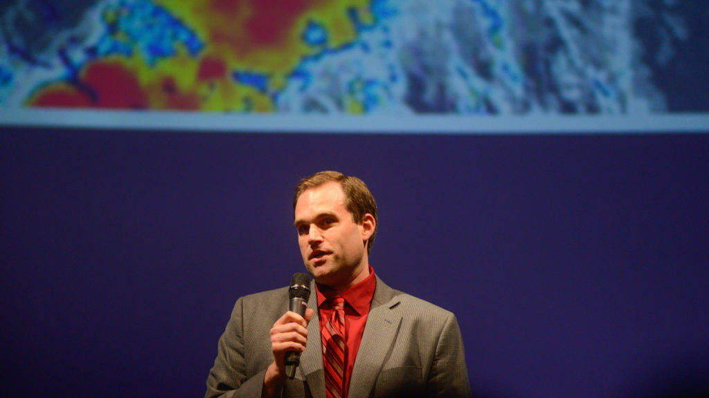 Michael Brennan holding a microphone in front of a satellite image of a hurricane