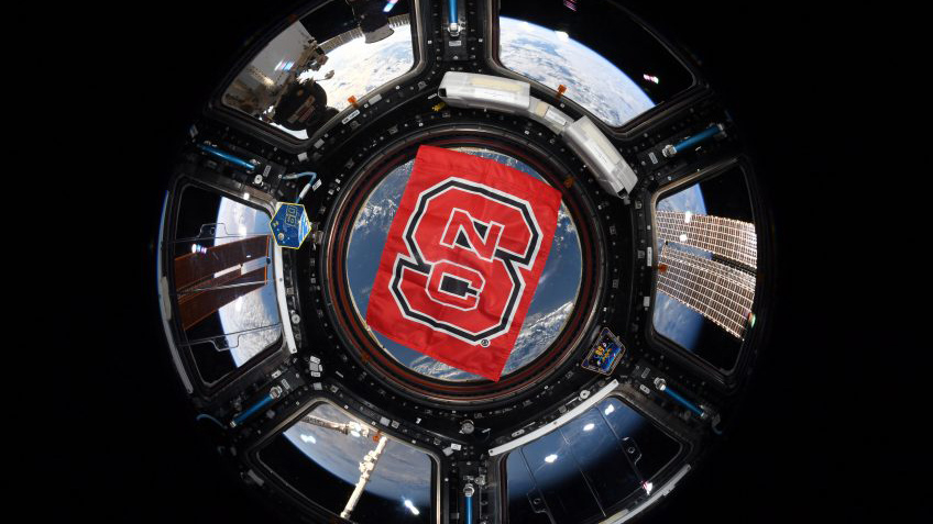 A red flag with the NC State block S hanging in the cupola of the International Space Station, with Earth in the background