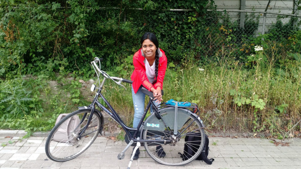 Sanjana Curtis leaning against a bicycle