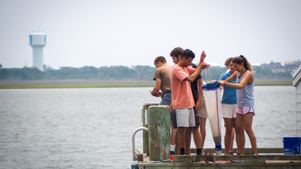 Students practice dredging for plankton off a pier at CMAST in Morehead City