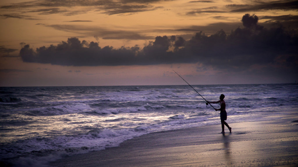 A fisherman on a beach casts his fishing rod into the ocean with the sun setting in the background