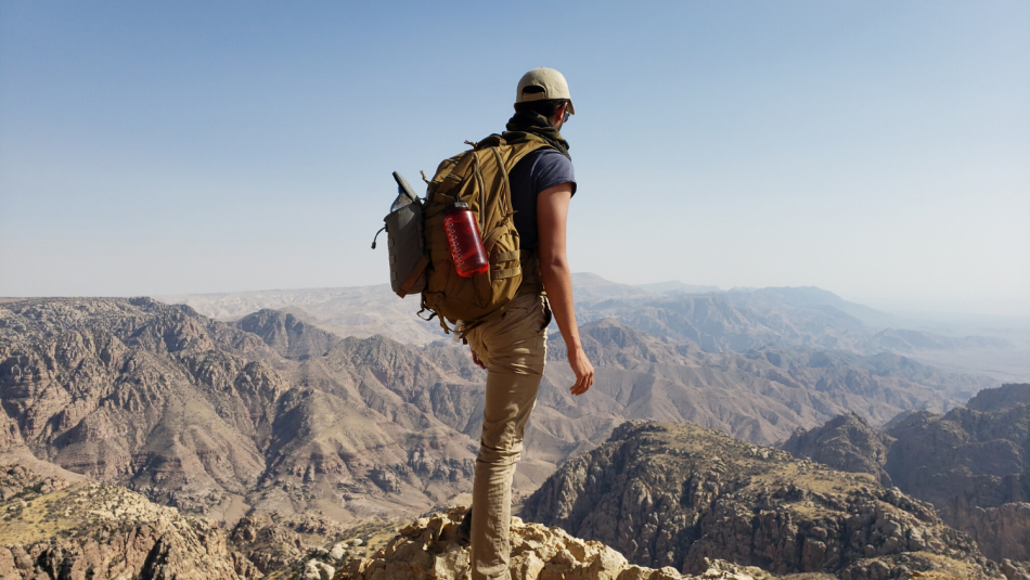 Hamil Vashi stands atop a mountain in Jordan