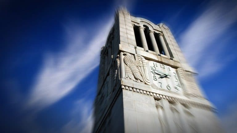 Top of NC State Belltower set against blue sky