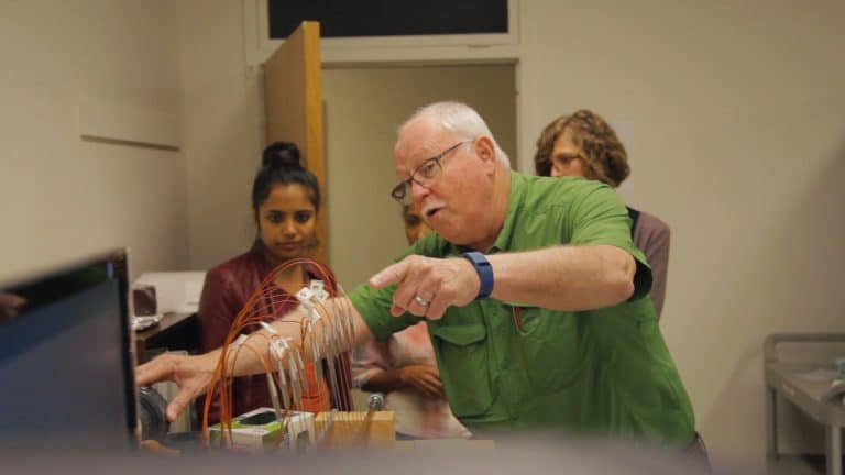Thomas Banks demonstrates an experiment to students in his lab