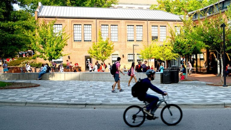 Student riding bike on NC State campus