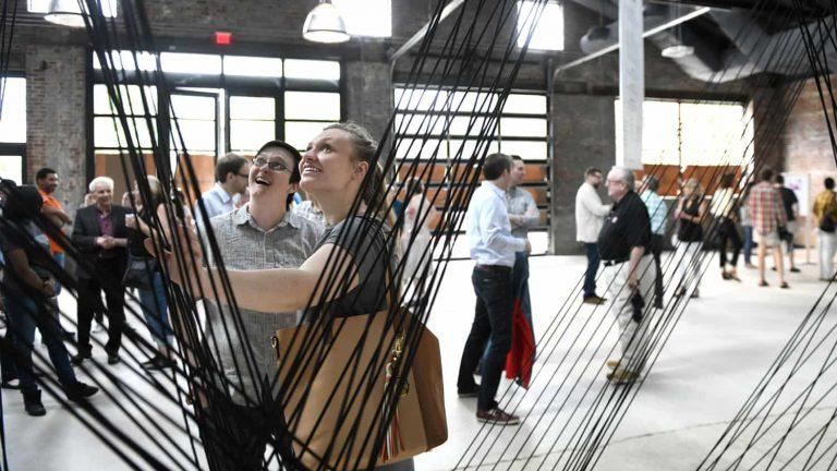 Two women among crowd enjoying the Leading strand exhibit