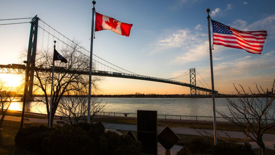 This photo depicts the Ambassador Bridge, as seen from Windsor, Ontario, Canada. The national flags of the USA and of Canada are in the foreground.