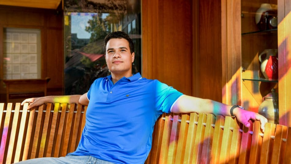 Yussef Guerrab sitting on a bench with brightly colored rays of light coming in
