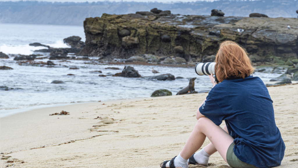 Kenzie Cromer sits on a beach taking a photo with a camera
