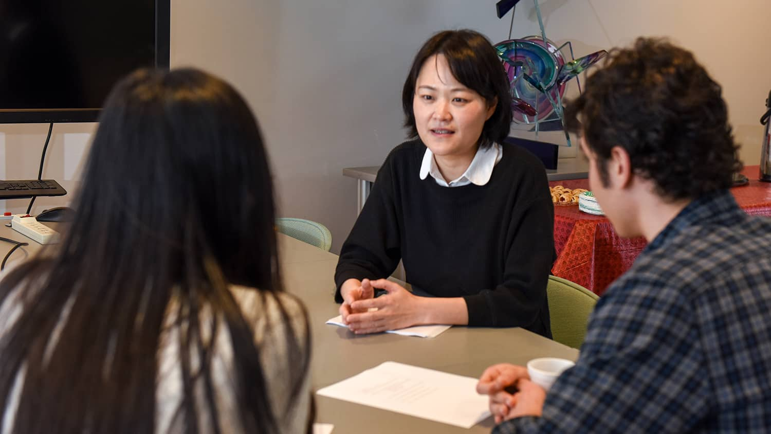 A faculty member talking with two students