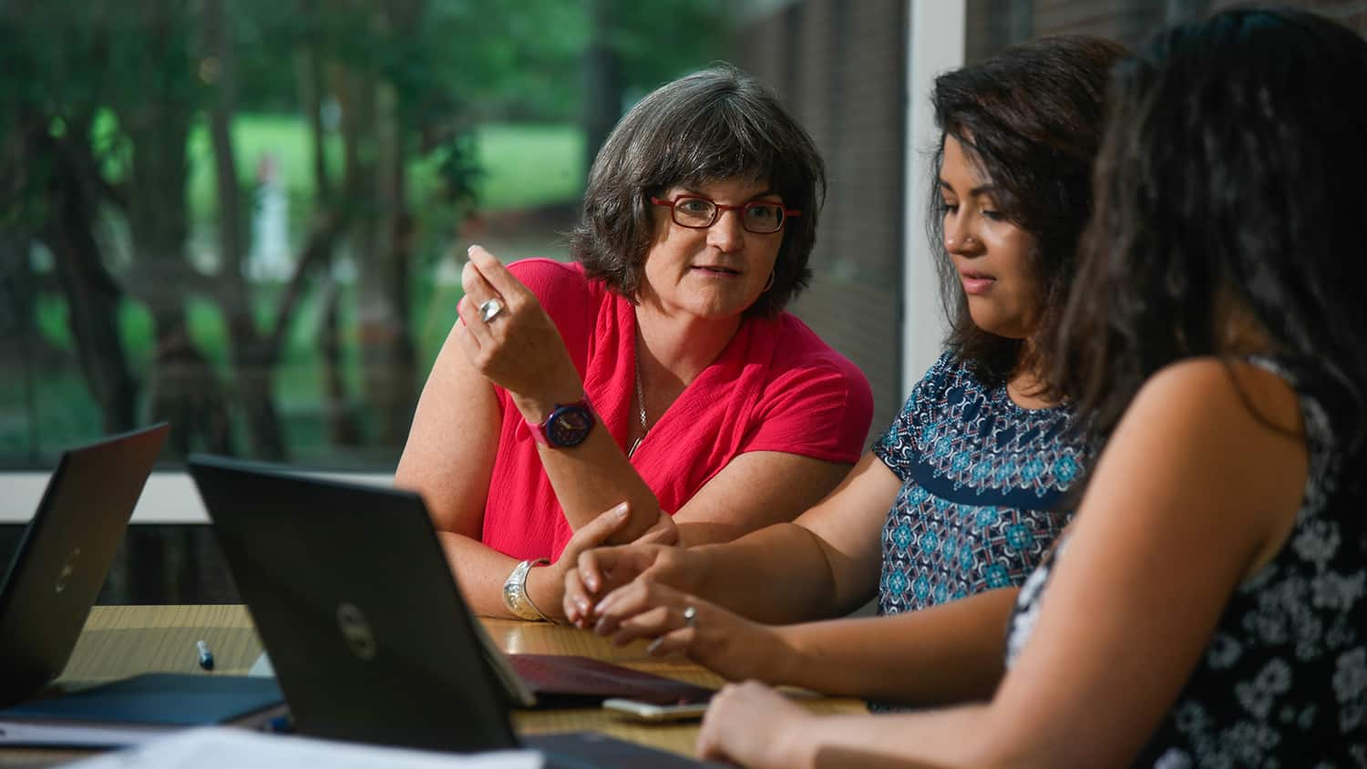 Professor Jane Hoppin speaks with two students sitting at a desk with laptops