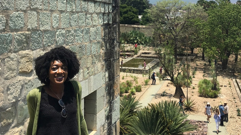 Modesty Obasohan sits on a stone wall in Mexico