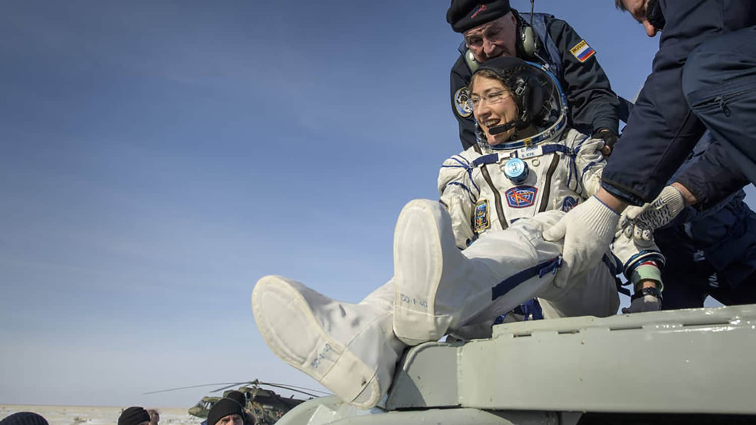 Christina Koch is helped out of a landing capsule on Earth