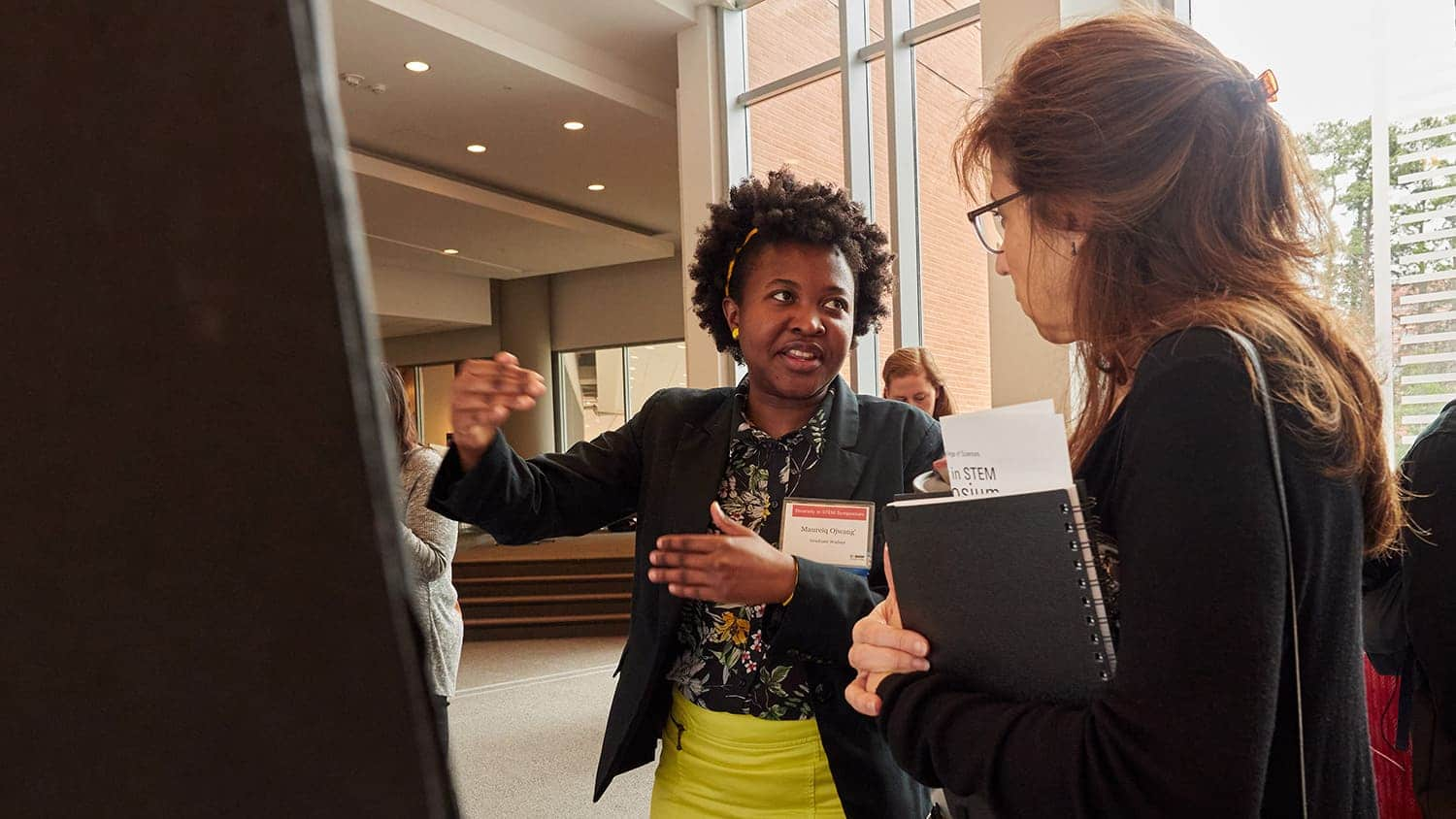 Ph.D. student Maureiq Ojwang' explains her research poster to an attendee.