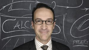 Robert Ghrist stands in front of a marked-up chalkboard
