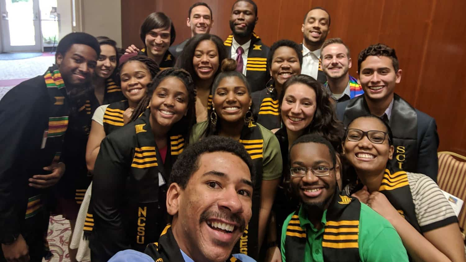 A group of diverse students pose for a selfie