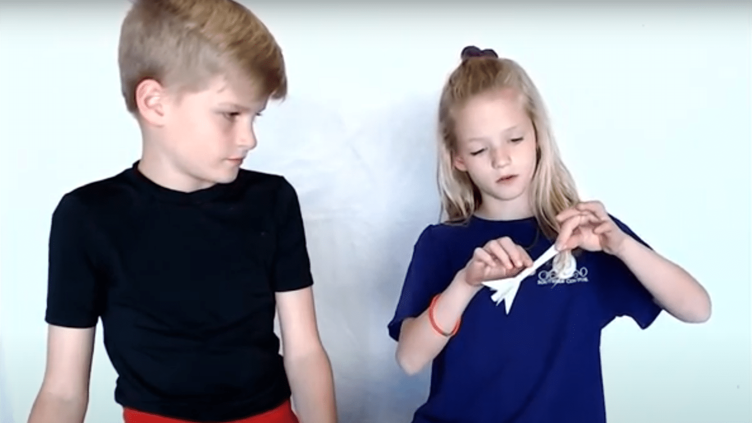 Two kids work on building a straw rocket