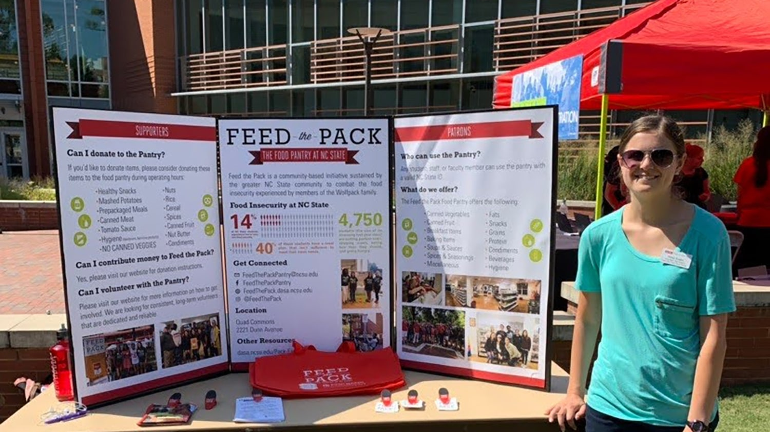 Rose Krebs standing next to a display about Feed the Pack on the Brickyard