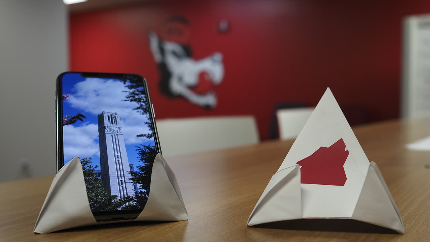 Two origami phone stands on a table, one holding a phone vertically and the other without a phone