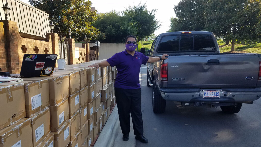 Volunteer stands next to a pickup truck and stacks of cardboard boxes containing virtual reality headsets