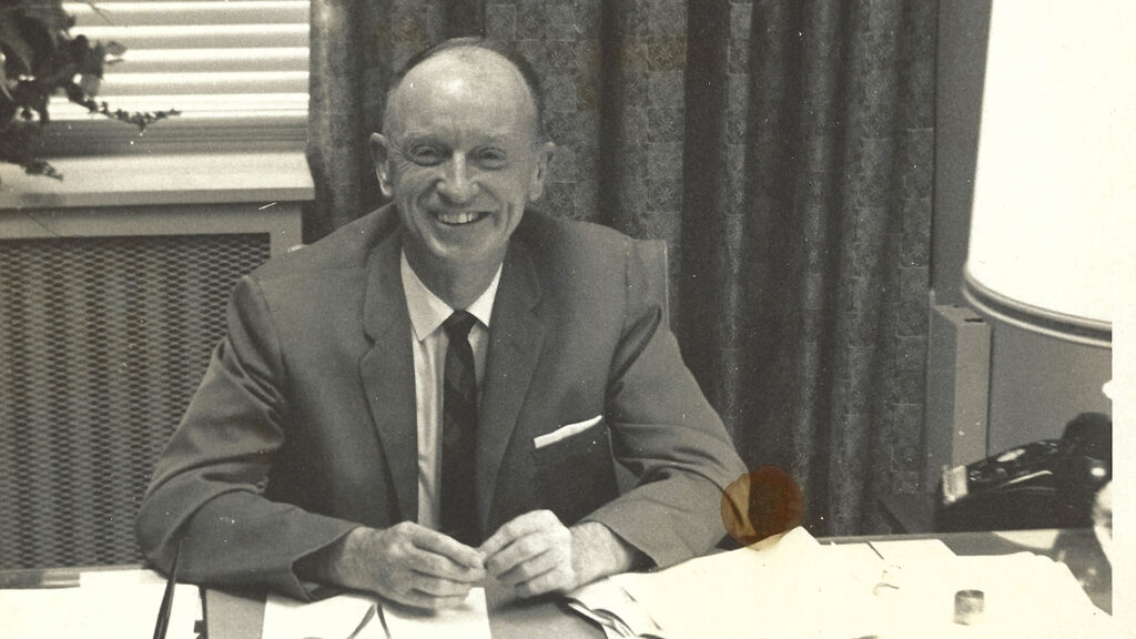 A black-and-white photo of Jack Stewart at his desk at NC State