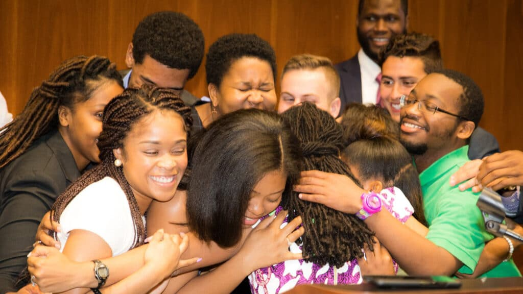 A large group of diverse students hug Jamila Simpson