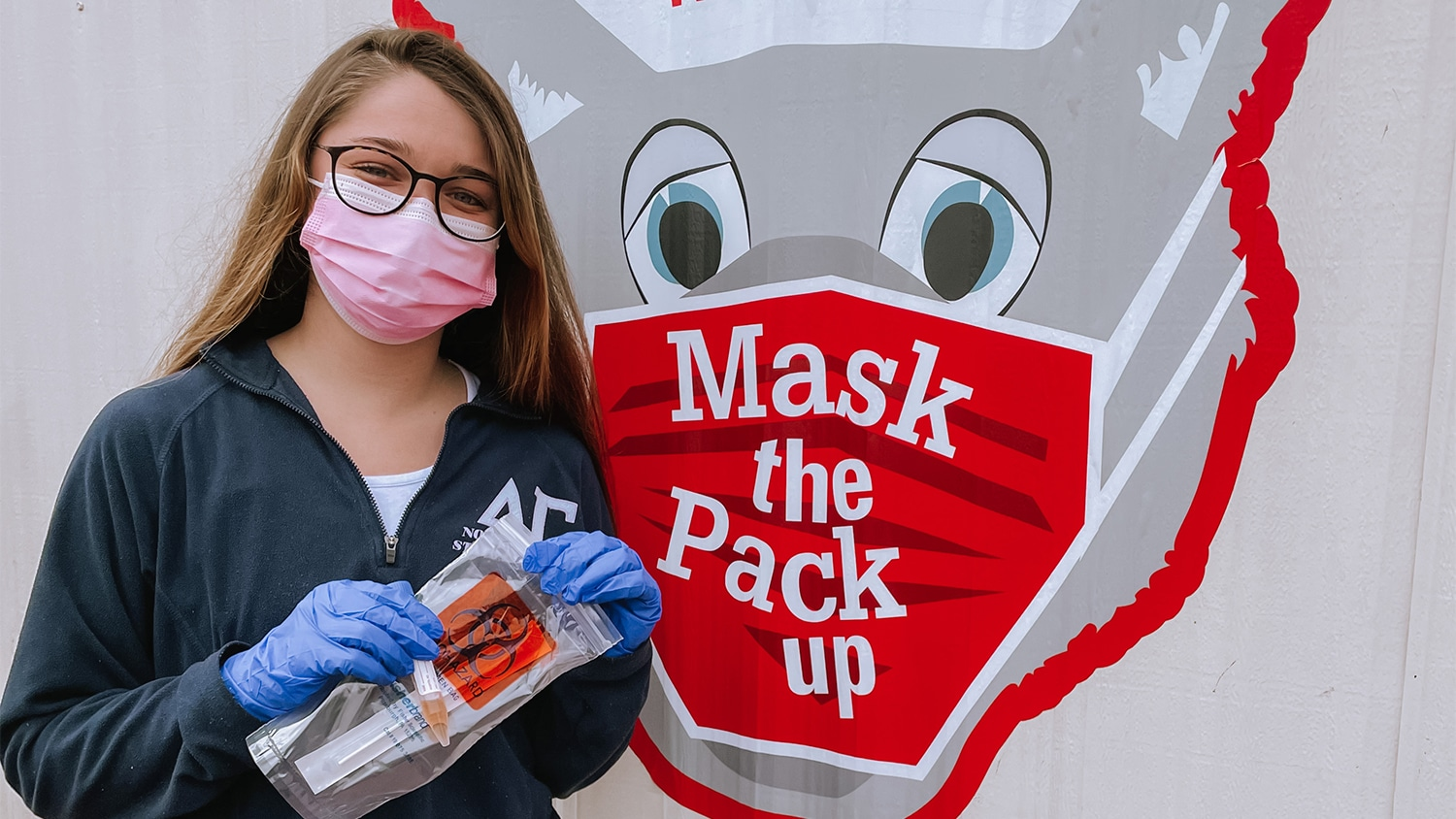 "A female student holds a COVID-19 test bag in front of a Mr. Wuf head sign that reads ""Mask the Pack Up"""