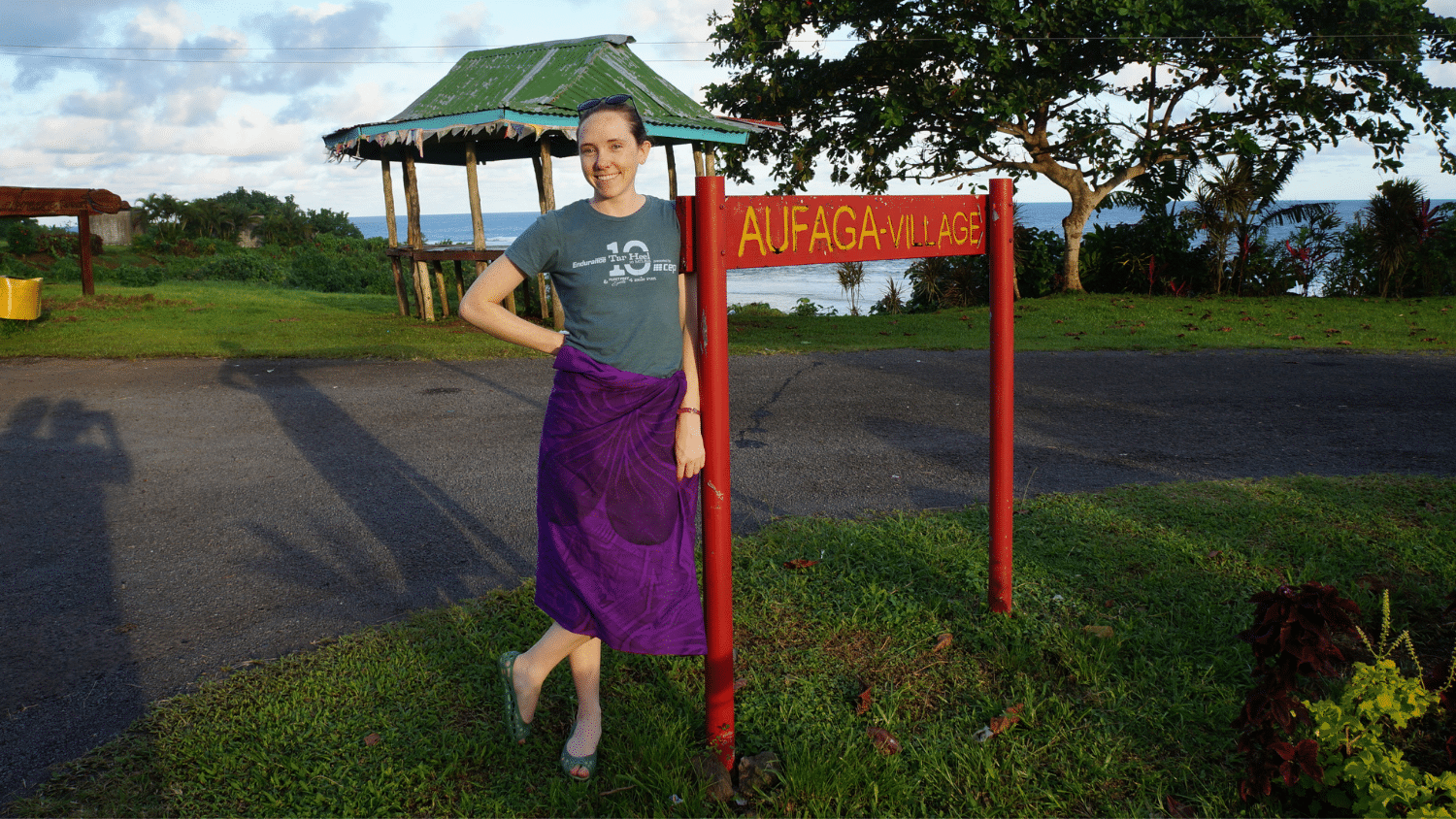 Natalie Ziemba stands in front of a sign that reads Aufaga Village