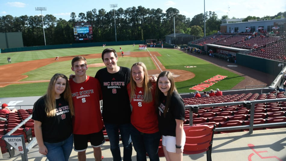 Five students wearing NC State shirts stand in front of the baseball diamond at Doak Field