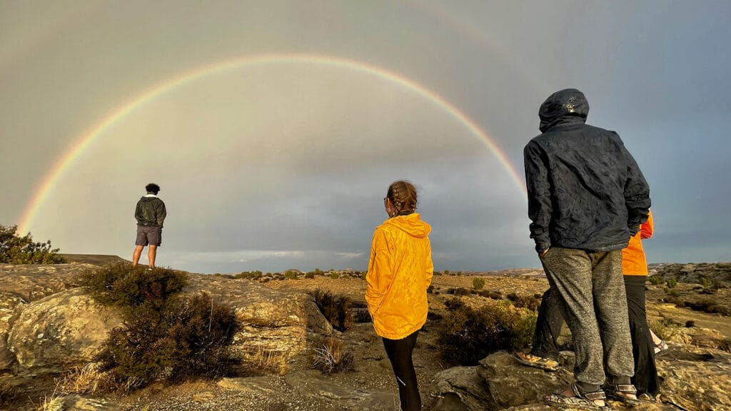 Several people look at a rainbow in the sky