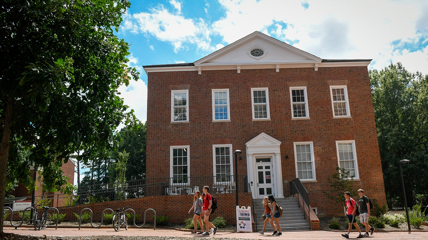Students walk past the Bureau of Mines building on NC State's campus
