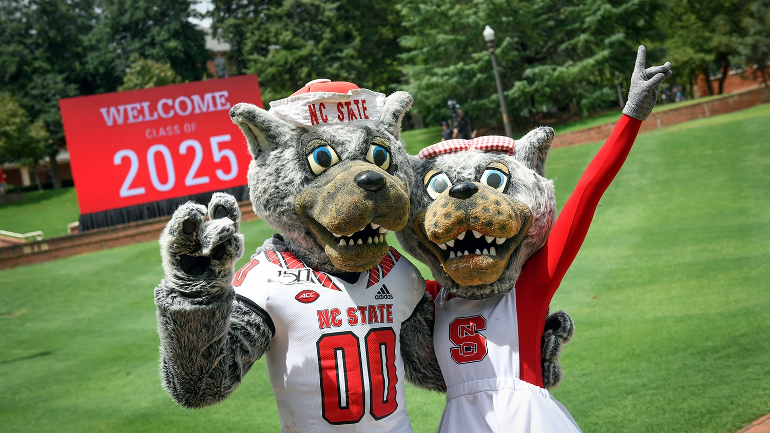 Mr. and Mrs. Wuf in front of a sign that says Welcome, Class of 2025