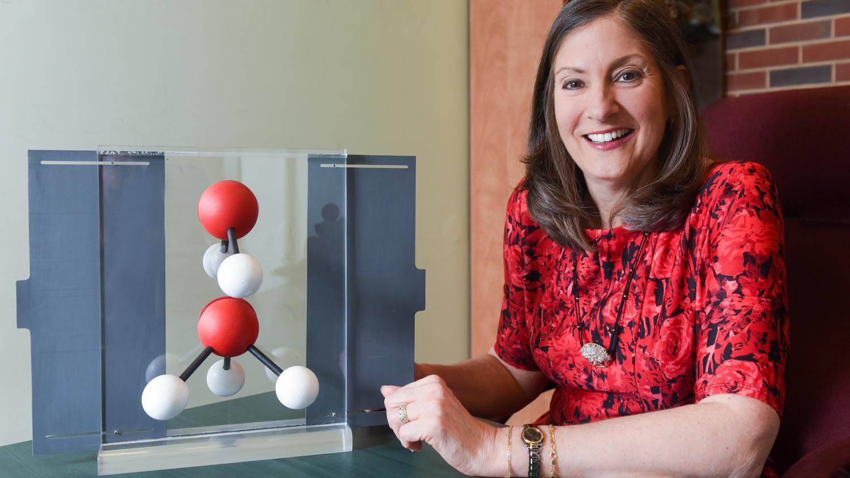 Maria Oliver-Hoyo at a desk with a molecular model