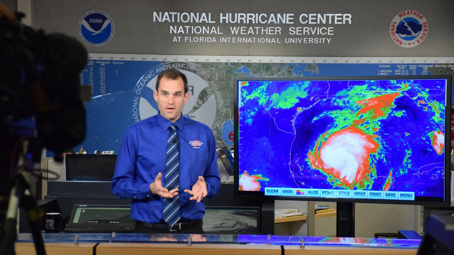 Michael Brennan stands next to a satellite image of a hurricane on a screen in the National Hurricane Center