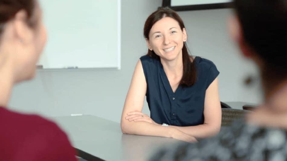 Lorena Bociu sitting at table with students.