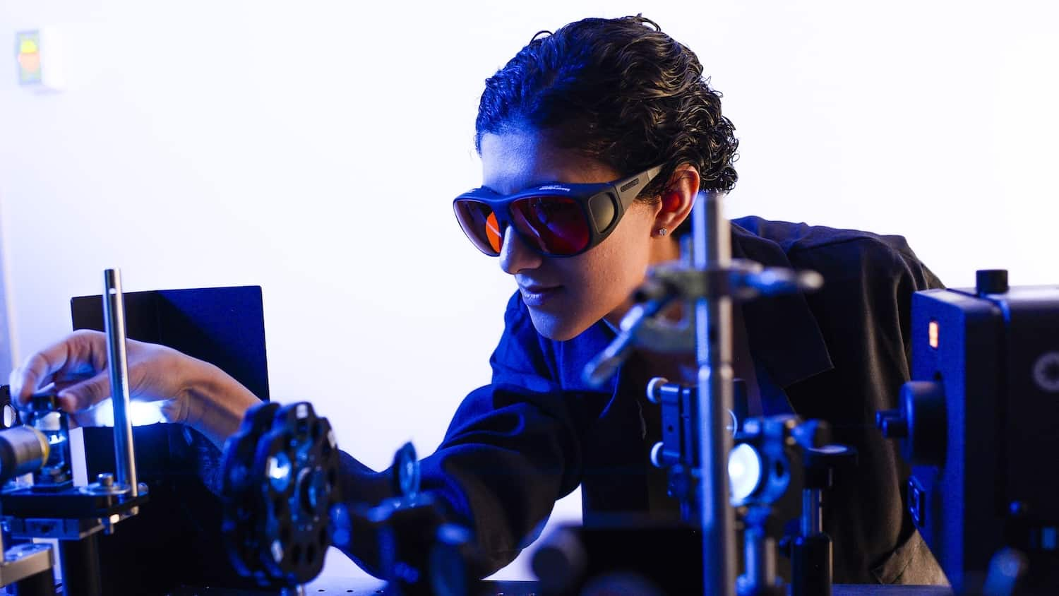 A female student in lab goggles examines a piece of photochemistry equipment