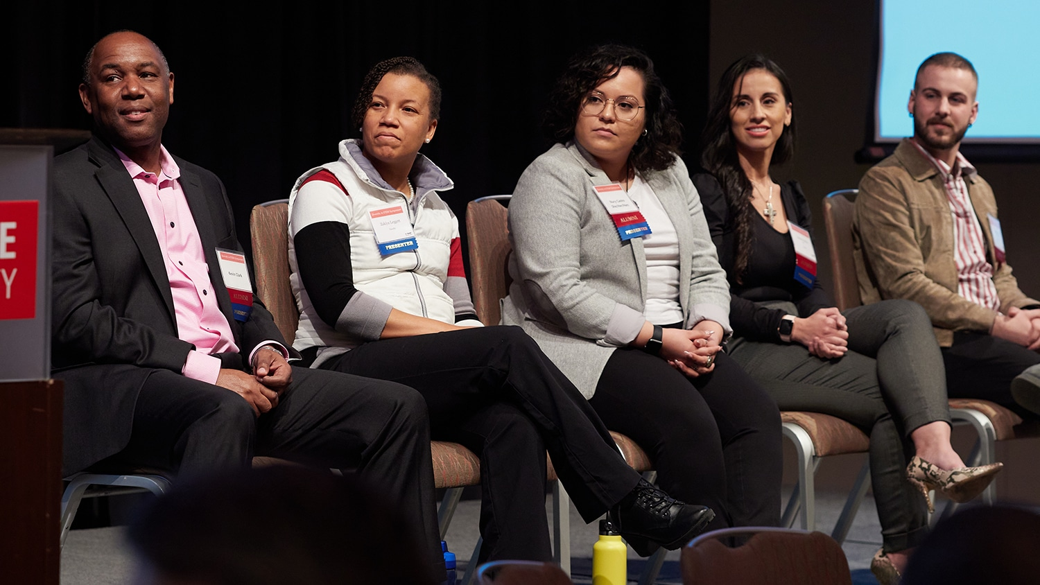 Five panelists at a symposium event sit on stage